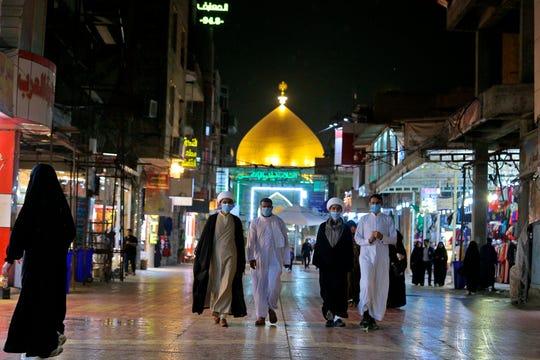 In this Monday, Feb. 24, 2020, Shiite pilgrims wear masks outside the shrine of Imam Ali in Najaf, Iraq.