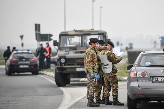 Italian Army soldiers and police check transit to and from the cordoned areas near Turano Lodigiano, Northern Italy, Tuesday, Feb. 25, 2020.