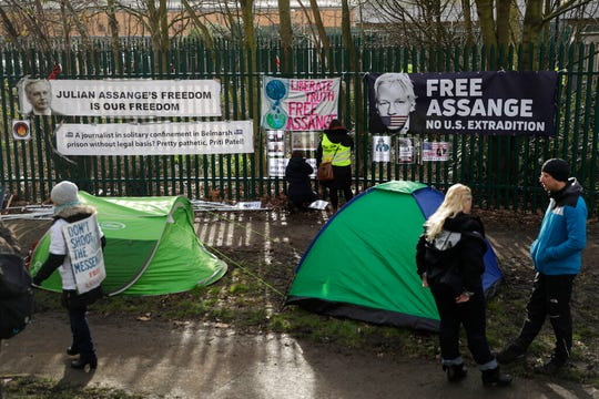 Supporters of Julian Assange tape up protest messages on a fence by supporters' tents on the second day of a week of opening arguments for the extradition of Wikileaks founder Julian Assange outside Belmarsh Magistrates' Court in south east London, Tuesday, Feb. 25, 2020.
