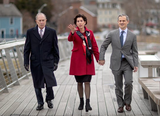 Democratic presidential candidate and former New York City Mayor Michael Bloomberg, left, walks with Rhode Island Gov. Gina Raimondo, center, and her husband, Andrew Moffit, over a recently opened pedestrian bridge to a campaign event for Bloomberg, in Providence, R.I., on Feb. 5.