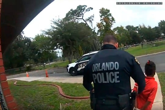 In this image taken from Sept. 19, 2019, Orlando Police Department body camera video footage, Orlando Police Officer Dennis Turner leads 6-year-old Kaia Rolle away after her arrest for kicking and punching staff members at the Lucious & Emma Nixon Academy Charter School in Orlando, Fla.