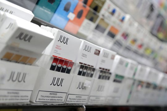 FILE - In this Dec. 20, 2018, file photo, Juul products are displayed at a smoke shop in New York. On Wednesday, Feb. 12, 2020, On Wednesday, Feb. 12, 2020, Massachusetts sued Juul Labs Inc., accusing the company of deliberating targeting young people through its marketing campaigns. (AP Photo/Seth Wenig, File)