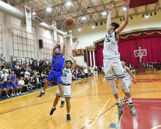 The Father Duenas Friars face the Saint Paul Warriors in IIAAG Boys Basketball in this Feb. 25 file photo. The two teams will battle for the title on Friday.