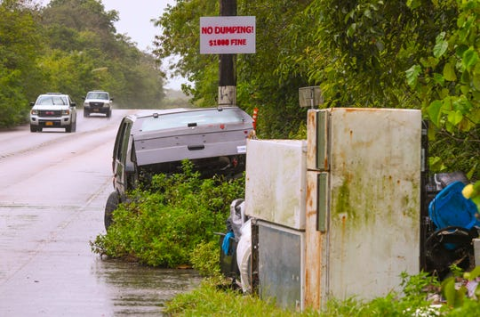 An abandoned vehicle, multiple white good appliances and other discarded debris can be found near the base of a utility pole with a sign, stipulating the penalty for illegal dumping, along Bumuchachu Street in Dededo on Tuesday, Feb. 25, 2020.