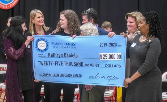 Kathryn Daniels, Petal High School history teacher, middle, holds a check for the Milken Educator Award for $25,000 with former Milken Educator Award recipients during a surprise assembly in the Petal High School gym Tuesday, Feb. 25, 2020.