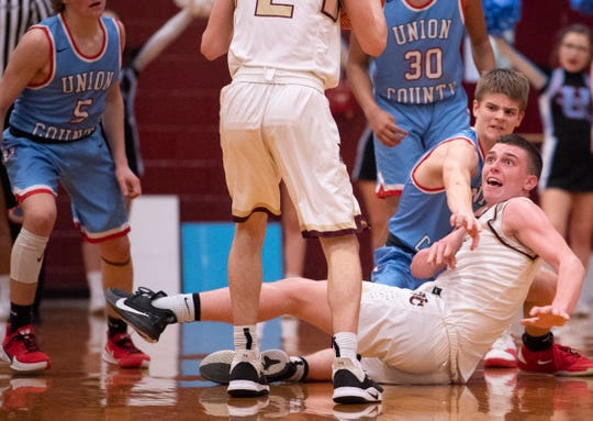 Webster County's Zaine Geary, bottom right, narrowly complete a pass to Webster County's Tyler Camplin (2) while being defended by Union County's Eli Mackey (10) during their Sixth District Tournament game at Webster County High School Monday night, Feb. 24, 2020.