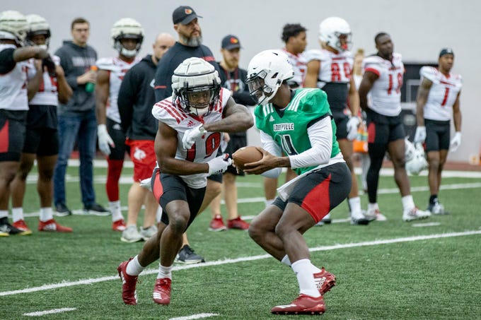 Running back Hassan Hall, left, takes a handoff from quarterback Jawon Pass during a UofL football practice at the indoor Trager Center on Monday. Feb. 24, 2020