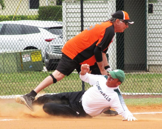Stonewalls Jon Krebs slides in third base trying to beat the ball as Sand Bar's Jerry Engel gets the putout.
