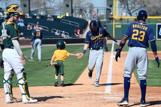 Brewers third baseman Lucas Erceg slaps hands with a bat boy as Erceg approaches home plate after hitting a two-run home run against the Oakland Athletics during the second inning of a spring training game at HohoKam Stadium.