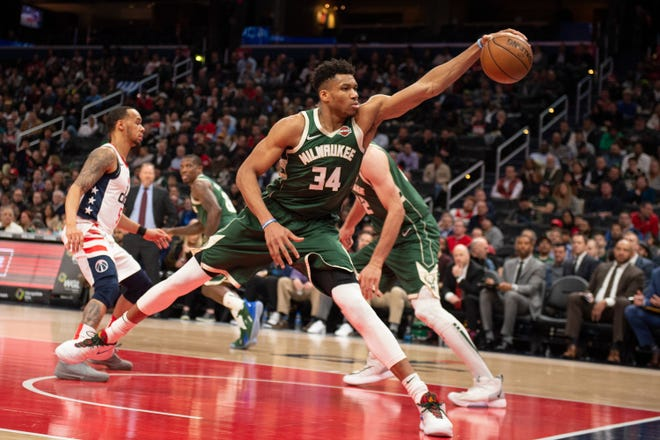 Bucks forward Giannis Antetokounmpo reaches for the ball before it goes out of bounds during the first half against the Wizards.