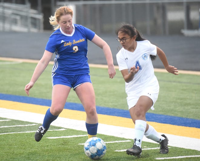 Mountain Home's Lauren Helmert battles Harrison's Eliana Adamos for possession of the ball on Monday night at Bomber Stadium.