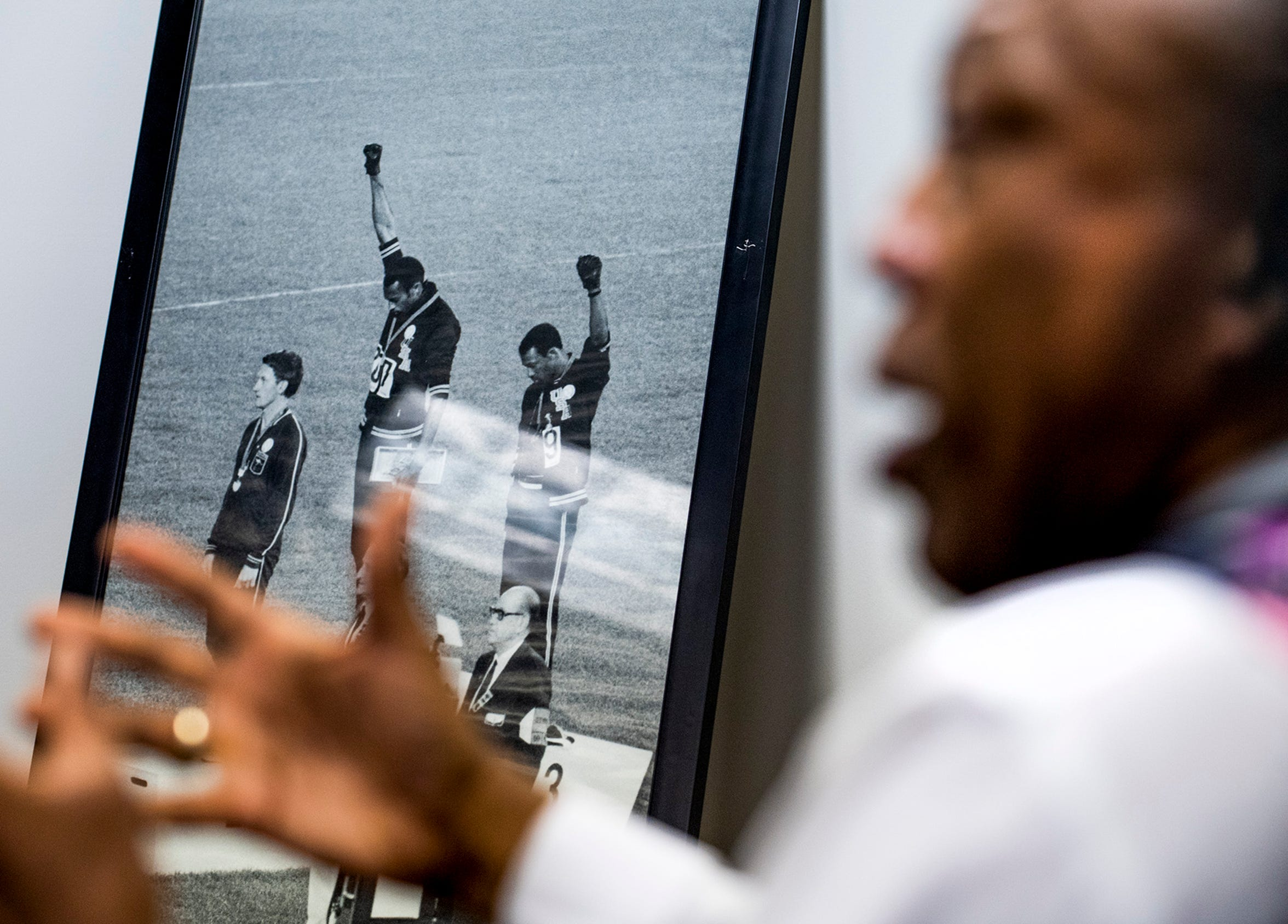 A photo of 1968 U.S. Olympic medalists Tommy Smith, center, and John Carlos raising the black power sign, is displayed in the office of  sports attorney Don Jackson in Montgomery, Ala., on Monday February 24, 2020.