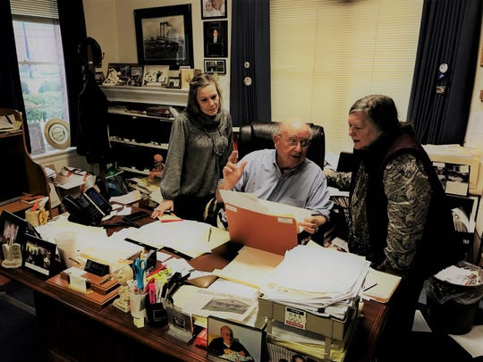Julian McPhillips in his office with a client and attorney.