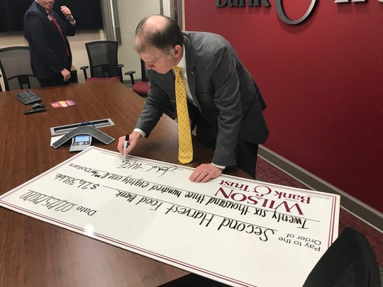 Wilson Bank & Trust CEO John McDearman signs the bank's big check to Second Harvest Food Bank.