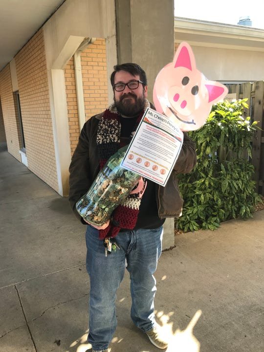 TJ Garton, a teacher at Belle Meade Children's Center, shows off the special piggy bank the children filled as part of the Ms. Cheap Penny Drive for Second Harvest Food Bank.