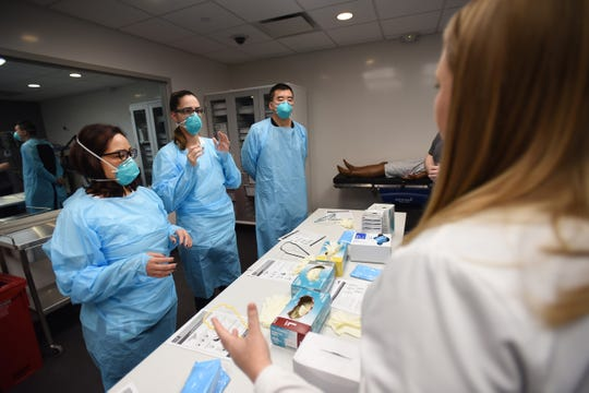 Ashley Blanchard (foreground), Manager, Infection Prevention, leads a training as (L to R), Nurse Jennifer Tempo, RN, Nurse Viviana Castano, RN, and Doctor Jesson Yeh, MD, are being trained during the Covid 19 Training with Personal Protective Equipment (PPE) at the hospital's simulation center at Holy Name Medical Center in Teaneck on 02/24/20.