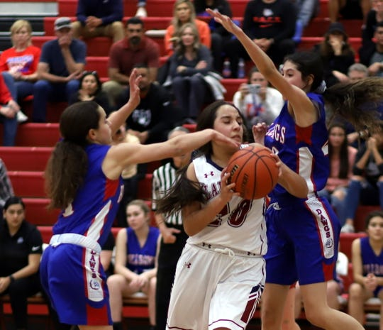 Senior Lady 'Cat guard Nicole Lopez (10) maneuvered through heavy traffic during Deming's 48-38 victory over the Las Cruces High Bulldawgs.