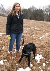 Kristy Green stands outside Green Acres Labs in Highland on Feb. 25 with her seven month old Labrador puppy Olive. Olive is being raised by Green to become an emotional support dog for the South Lyon Community School District and should be ready to go for the fall of 2020.