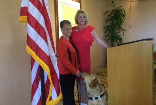 Marie Hoesman, representing the Braille Institute, shows off her guide dog, Noelle.