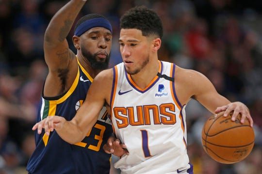 Phoenix Suns guard Devin Booker (1) brings the ball up court as Utah Jazz forward Royce O'Neale (23) defends in the second half during an NBA basketball game against the Utah Jazz Monday, Feb. 24, 2020, in Salt Lake City. (AP Photo/Rick Bowmer)