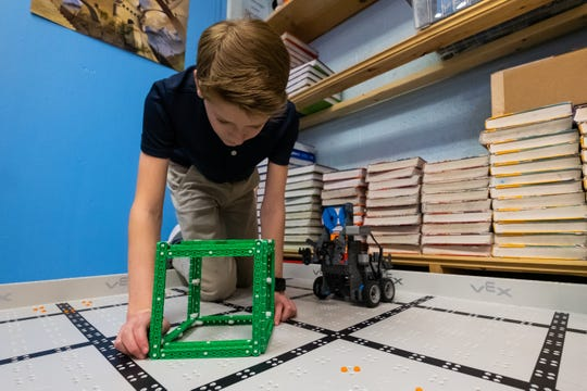 New Life Christian Academy eight-grader Ben Gura sets up a test run of his team's robot Tuesday, Feb. 25, 2020, during the school's robotics team's practice.