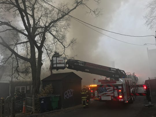 City of Poughkeepsie firefighters assist with a fire on Market Street in Wappingers Falls Tuesday.