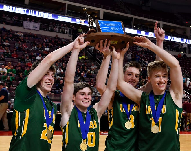 York Catholic captains Dylan Durbin, left, Owen Leese, Benjamin Nelson-Moir, and Benjamin Curtis hold the District 3 Class 2-A boys' basketball championship trophy in the air after defeating Millersburg 47-46, Monday, February 24, 2020.