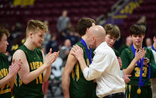 York Catholic head coach Dustin Boeckel hugs his son, Preston, after putting a gold medal around his neck to celebrate the Irish's District 3 Class 2A title win Monday. Preston scored 11 points in the win over Millersburg.