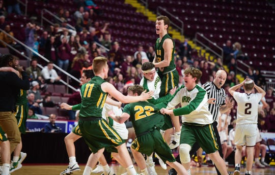 The York Catholic boys' basketball team celebrated after beating Millersburg, 47-46, for the District 3 Class 2A title at the Giant Center Monday.