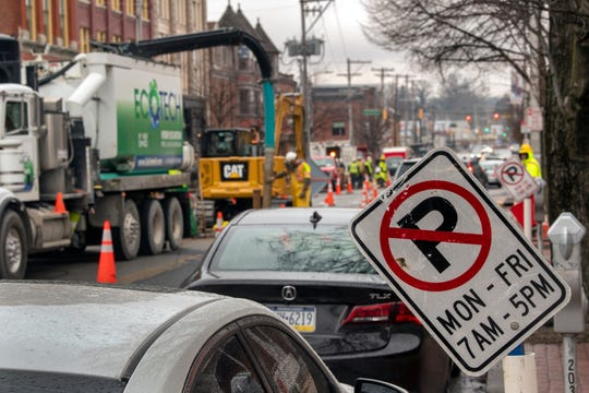 No parking signs replace metered parking spaces along North George Street In York while a specialized machine removes soil around multiple utility lines so they aren't damaged in reaching the water main below them.