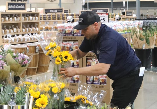 David Silva of San Jose, Northern California operations specialist for produce at Sprouts Farmers Market, arranges sunflowers at the new grocery store in the Mt. Shasta Mall on Tuesday, Feb. 25, 2020, ahead of the store's opening Wednesday morning.