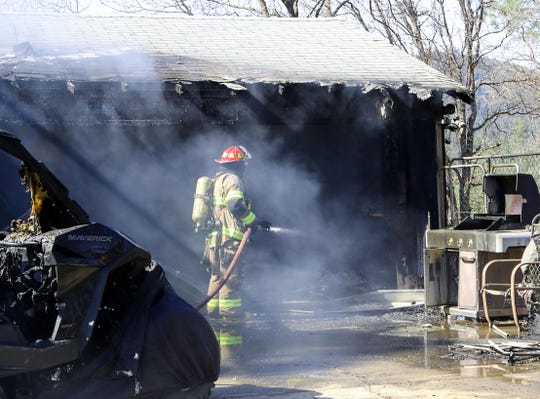 A firefighter hoses down a garage that burned along with an attached home at 3701 Altus Street in Shasta Lake on Tuesday afternoon.