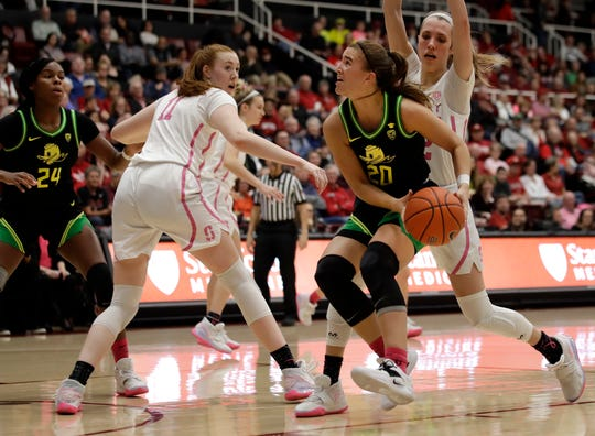 Oregon's Sabrina Ionescu (20) looks to shoot between Stanford's Ashten Prechtel (11) and Lexie Hull, right, in the first half of an NCAA college basketball game Monday, Feb. 24, 2020, in Stanford, Calif.