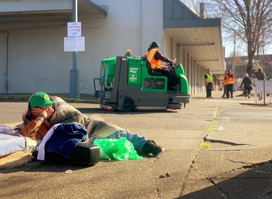 A homeless man who would not give his name rests while crews from ServiceMaster clean and sanitize the sidewalks outside the Rite Aid in downtown Salem, February 25, 2020. Signs were posted closing the sidewalk for the day while the cleaning and sanitizing took place.