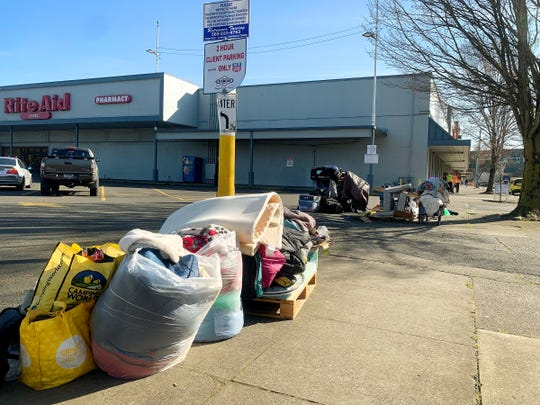 Stacks of items from the area around the Rite Aid are stacked near the parking lot as crews from ServiceMaster clean and sanitize the sidewalks outside the Rite Aid in downtown Salem, February 25, 2020. Signs were posted closing the sidewalk for the day while the cleaning and sanitizing took place.
