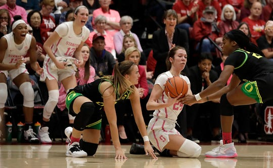 Oregon's Ruthy Hebard, right, and Sabrina Ionescu try to steal the ball from Stanford's Lacie Hull (24) during the first half of an NCAA college basketball game Monday, Feb. 24, 2020, in Stanford, Calif.