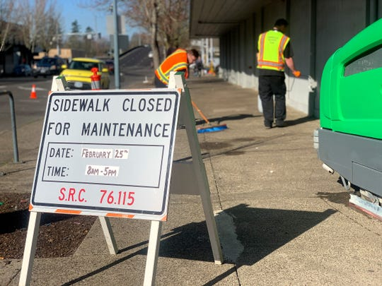 Crews from ServiceMaster clean and sanitize the sidewalks outside the Rite Aid in downtown Salem, February 25, 2020. Signs were posted closing the sidewalk for the day while the cleaning and sanitizing took place.