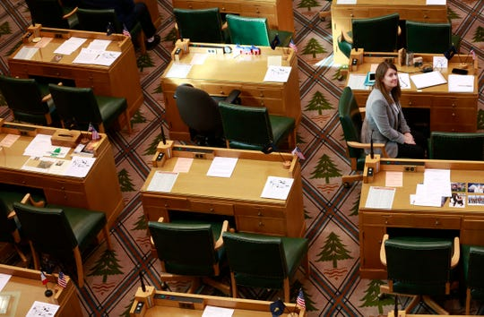 Rep. Cheri Helt, R-Bend, sits among the empty desks of her Republicans colleagues in the Oregon State Capitol Building in Salem, Oregon, on Tuesday, February 25, 2020. House Republicans walked out of the Capitol on Tuesday in protest of a controversial greenhouse gas emissions cap-and-trade bill.