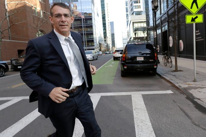 Michael Center, former men's tennis coach at the University of Texas at Austin, runs from federal court in Boston, Monday, Feb. 24, 2020, after being sentenced in a nationwide college admissions bribery scandal.