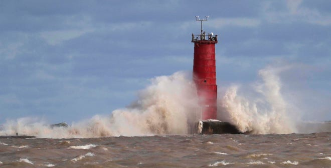 Strong waves crash against the Sheboygan lighthouse, Tuesday, February 25, 2020, in Sheboygan, Wis.