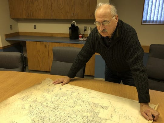 Amateur historian Steve Wegman looks over a mid-20th century map of Sioux Falls in his office in Pierre. Wegman, an amateur historian who is director of the South Dakota Renewable Energy Association, first alerted state officials about questions over ownership of land on the Sioux Steel Company site that is poised for redevelopment.
