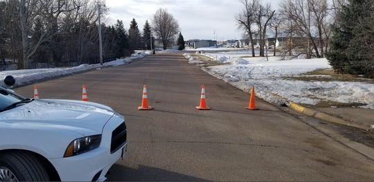Police sit outside of the scene where a driver hit and killed a pedestrian Monday in Hartford, South Dakota.
