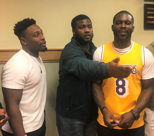 FAMU linebacker Ellrie Allen (left) and defensive lineman Jolan Gilley gather for a photo with Michael Vick during his visit to campus on Monday, Feb. 24, 2020.