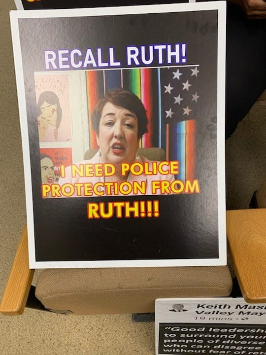 Even though the campaign to recall Simi Valley City Council member Ruth Luevanos has been suspended at least temporarily, an audience  member at Monday night's council meeting displayed a recall sign.