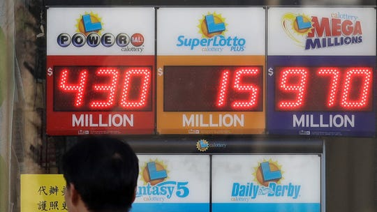 In this Oct. 18, 2018, file photo, a man walks past a lottery display outside of The Lucky Spot in San Francisco. A report released by the California state auditor says the lottery failed to provide adequate funding to education and that it should have accounted for an increase in profits in fiscal year 2017-2018 by turning over an additional $36 million to public schools. Lottery officials say they disagree with the auditor's accounting.
