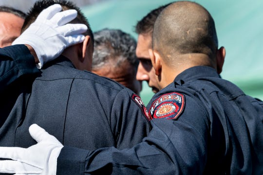 Pallbearers from Porterville Fire Department gather in grief after carrying Captain Ramon Figueroa to gravesite as firefighters from across California pay their respects in Delano on Tuesday, February 25, 2020.