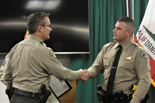 Tulare County Sheriff Mike Boudreaux shakes hands with deputy Jonathan Banda on Tuesday, February 25, 2020.