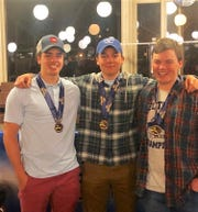 Mamaroneck's Cole Lovejoy, Robby Lundberg and Charlie Roseberry with their medals Monday night after all placed in the top 10 at the State Skiing Championships at Bristol Mountain.