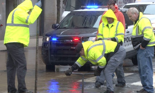 A worker tries to stop a water main break Tuesday morning in Wilmington at the intersection of 11th and Orange streets.