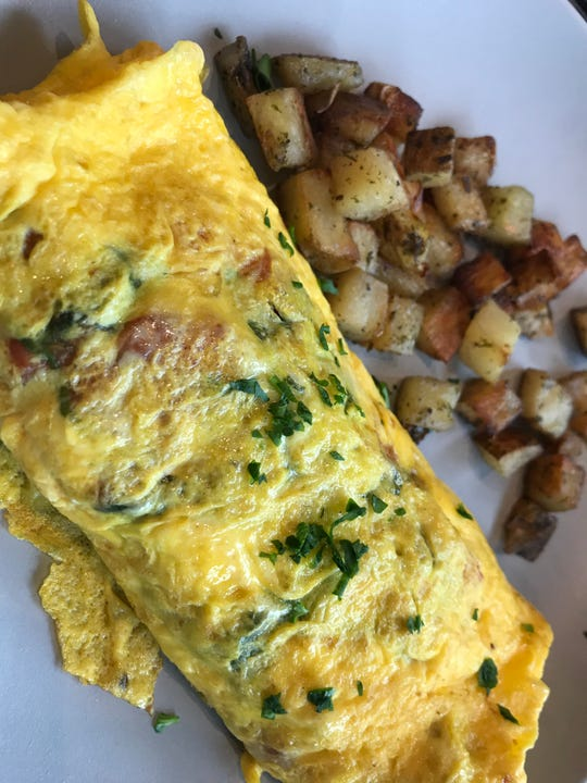 Omelets, served with breakfast potatoes, can be customized. This $10 order included goat cheese, tomatoes and spinach.